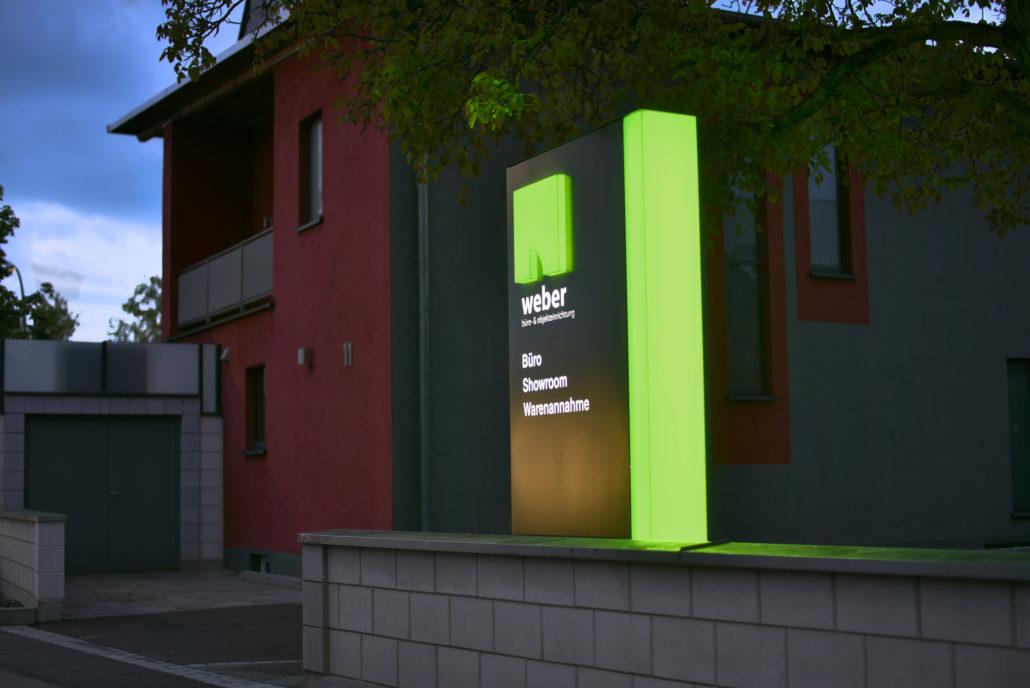 Gerader Pylon mit durchgestecktem Logo und beleuchteter Schrift