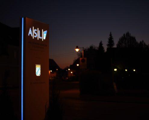 Werbepylon mit beleuchtetem Logo