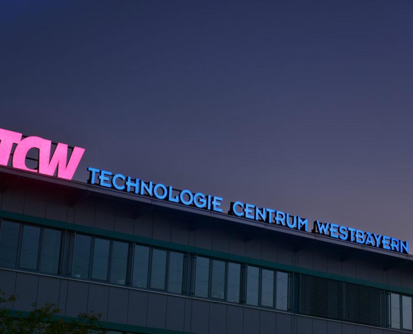 beleuchtetes Logo auf dem Dach eines Gebäudes